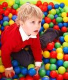 Bambino in sfere colourful. immagini stock