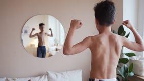 Bambino sicuro che esamina i suoi muscoli in specchio che immagina che sia eroe eccellente stock footage