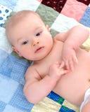 Bambino soddisfatto sulla trapunta Fotografie Stock