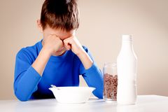 Bambino sonnolento che si siede alla tavola nelle prime ore del mattino Il ragazzo non vuole mangiare la sua prima colazione fotografia stock
