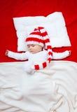 Bambino sonnolento sulla coperta rossa Fotografia Stock Libera da Diritti