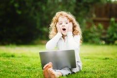 Bambino sorpreso colpito e felice con il computer portatile che si siede sul gra Fotografia Stock