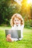 Bambino sorpreso colpito e felice con il computer portatile che si siede sul gra Immagini Stock