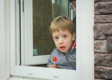 Bambino sorpreso con la caramella, esaminante fuori la finestra lo stre Fotografie Stock