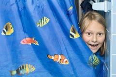 Bambino sorpreso dietro la tenda di acquazzone Immagine Stock