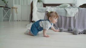 Bambino sorridente adorabile che striscia sul pavimento verso la macchina fotografica