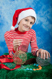 Bambino sorridente in cappello di Santa su fondo blu Immagini Stock