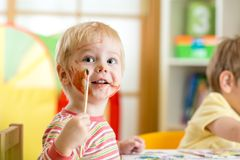 Bambino sorridente che dipinge a casa Fotografia Stock