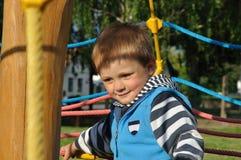 Bambino sorridente che gioca sul campo da giuoco Fotografie Stock Libere da Diritti