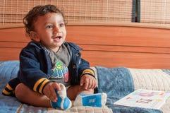 Bambino sorridente che ha divertimento con un libro Fotografia Stock