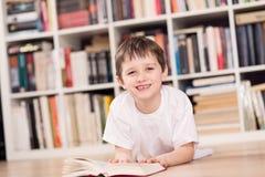 Bambino sorridente che legge un libro a casa Immagini Stock