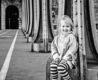 Bambino sorridente che si siede sul ponte di Pont de Bir-Hakeim a Parigi Immagine Stock