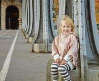 Bambino sorridente che si siede sul ponte di Pont de Bir-Hakeim a Parigi Fotografie Stock
