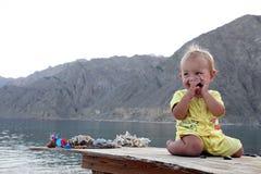 Bambino sorridente che si siede sulla tavola Fotografia Stock Libera da Diritti