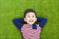 Bambino sorridente che si trova e che tiene la sua testa Fotografie Stock Libere da Diritti