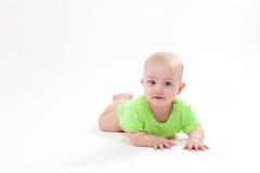 Bambino sorridente che si trova sul suo stomaco e sull'esame della macchina fotografica fotografia stock