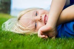 Bambino sorridente che si trova sull'erba all'aperto Fotografie Stock Libere da Diritti