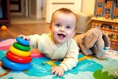 Bambino sorridente che si trova sulla sua pancia e che gioca con la piramide Fotografie Stock Libere da Diritti