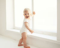 Bambino sorridente che sta nella stanza bianca a casa Immagine Stock Libera da Diritti
