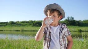 Bambino sorridente con bicchiere d'acqua in mani su prato inglese verde vicino al lough video d archivio