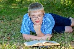 Bambino sorridente con un libro Fotografie Stock Libere da Diritti