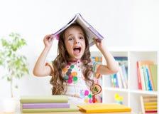 Bambino sorridente con un libro sopra la sua testa in primario Immagine Stock