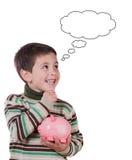 Bambino sorridente con un pensiero di salvadanaio Immagini Stock Libere da Diritti