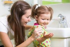 Bambino sorridente della ragazza e le sue mani di lavaggio della mamma e Fotografia Stock