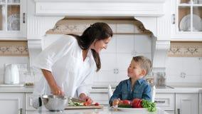 Bambino sorridente di agilità che ruba o che prende fetta di alimento mentre la madre sta cucinando stock footage