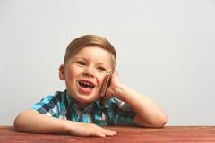 Bambino sorridente divertente che gioca con lo smartphone Immagini Stock