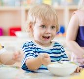 Bambino sorridente divertente che mangia dal piatto nell'asilo fotografia stock