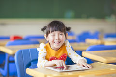 Bambino sorridente facendo uso della compressa o del ipad Fotografia Stock Libera da Diritti