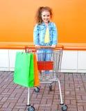 Bambino sorridente felice in carretto del carrello con i sacchetti della spesa Fotografia Stock
