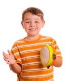 Bambino sorridente felice che gioca tambourine Fotografia Stock