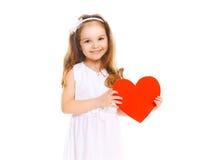 Bambino sorridente felice della bambina con grande cuore di carta rosso su bianco Fotografie Stock Libere da Diritti