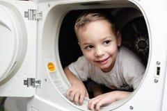 Bambino sorridente nell'essiccatore fotografia stock