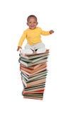 Bambino sorridente sui libri di un'alta torre Immagini Stock Libere da Diritti