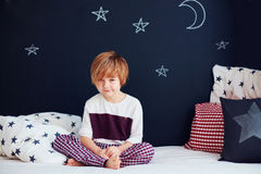 Bambino sorridente sveglio in pigiami che si siedono sul letto nella stanza della scuola materna immagine stock