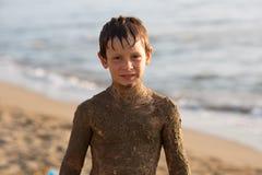 Bambino sporco del ragazzo della sabbia bagnata che sorride mentre giocando alla spiaggia Indicatore luminoso caldo di tramonto I Fotografie Stock