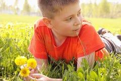 Bambino su erba con i denti di leone che osservano obliquamente fotografia stock libera da diritti