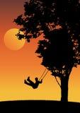 Bambino su oscillazione nel tramonto. Immagini Stock