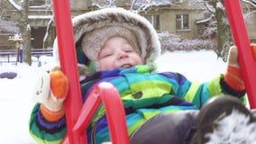 Bambino su oscillazione nell'inverno video d archivio