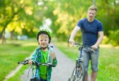 Bambino su un'acqua della bevanda della bicicletta con il padre nel parco fotografie stock libere da diritti