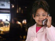 Bambino sul cellulare in ristorante fotografie stock