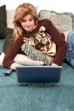 Bambino sul pavimento con il computer portatile Fotografia Stock