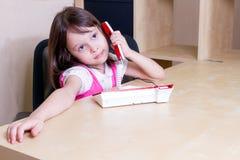 Bambino sul telefono in ufficio Immagine Stock