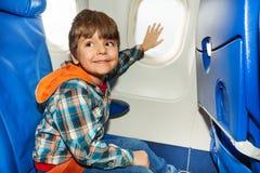 Bambino sulla finestra di tocco dell'aeroplano con la mano Fotografie Stock Libere da Diritti