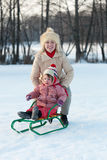 Bambino sulla slitta con la madre nell'inverno Immagine Stock