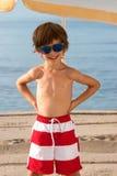 Bambino sulla spiaggia sotto l'ombrello con gli occhiali da sole Fotografia Stock