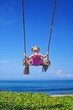 Bambino sulla volata su sull'oscillazione della corda sulla spiaggia del mare Fotografie Stock Libere da Diritti